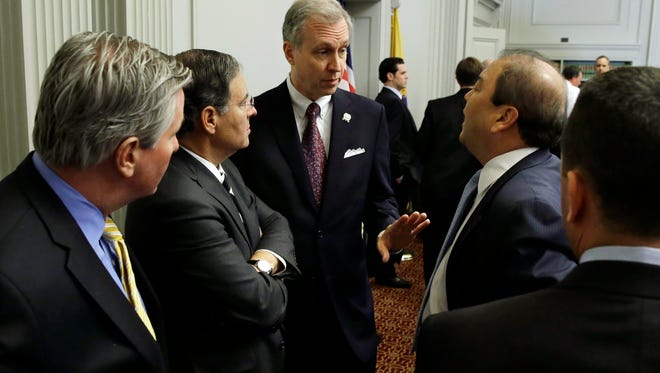 New Jersey Assemblyman John S. Wisniewski, center, D-Sayreville, N.J., co-chair of a joint bipartisan committee of members of the New Jersey Senate and Assembly, talks with Republican Assembly Leader, Jon M. Bramnick, second left, R-Westfield, N.J., and Sen. Kevin J. O'Toole, R-Wayne, N.J., second from right, and others before a meeting at the Statehouse in Trenton, N.J., Monday, Feb. 10, 2014. More subpoenas were issued by a New Jersey legislative committee investigating a plot to create gridlock by blocking lanes near the George Washington Bridge.