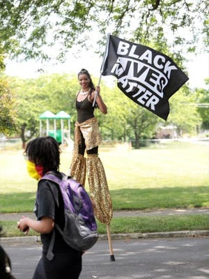 "A stiltwalker carries a ""Black Lives Matter"" sign during a Juneteenth celebration at the King Arts Complex."