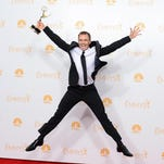 "Phil Keoghan poses in the press room with the award for Outstanding Reality - Competition Program for ""The Amazing Race"" at the 66th Annual Primetime Emmy Awards at the Nokia Theatre L.A. Live on Monday, Aug. 25, 2014, in Los Angeles. (Photo by Jordan Strauss/Invision/AP)"