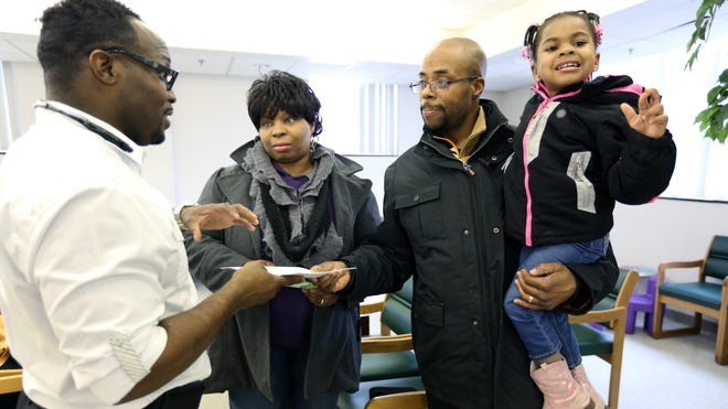 Isaiah Johnson, a certified application counselor at Advantage Health Center Thea Bowman clinic in Detroit, hands over an application to Keith Graves, 40, who was there in March with daughter Shakayla, 4, and wife Juliet, 44, all of Detroit.