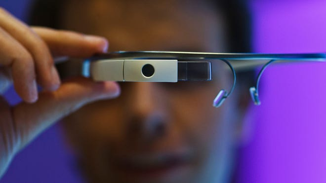 An employee holds a pair of Google Glass connected glasses at the Mobile World Congress in Barcelona, Spain, on Feb. 26, 2014.