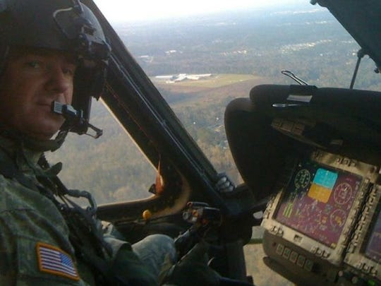 John Clement at the seat of a UH-60 Black Hawk helicopter.