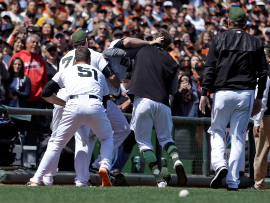 San Francisco Giants including George Kontos (70) and Mac Williamson (51) assist in escorting Hunter Strickland off the field after a brawl with the Washington Nationals in the eighth inning of a baseball game Monday, May 29, 2017, in San Francisco. (AP Photo/Ben Margot)