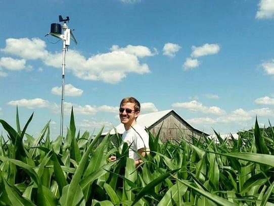 Alex Adams, CEO of GeoAir, poses in a corn field in