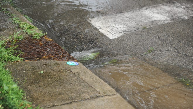 Water rushes into a sewer on South 14th Street north of the intersection with South A Street.