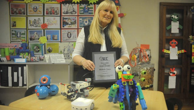 Michelle Vance holds her award while standing next to several robots she uses in grades 2 through 5 at Bucyrus Elementary School.