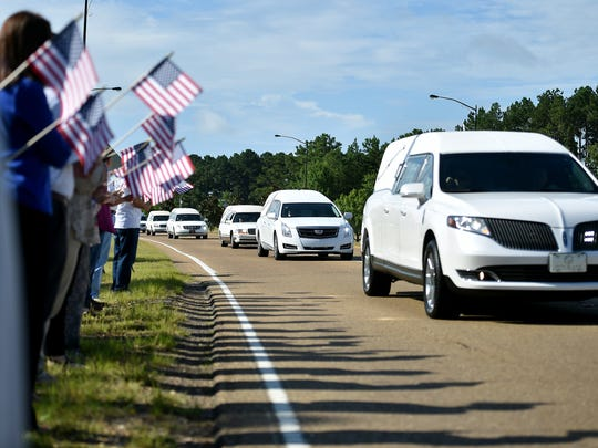Supporters hold American flags on the side of Airport Road in Jackson Thursday, July 13, 2017, as hearses carry the remains of the 16 servicemembers who died in a plane crash in Leflore County Monday, July 10, 2017, to the Air National Guard base for their final flight home.