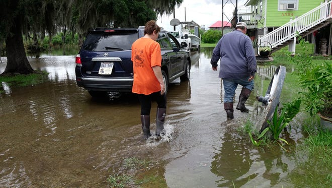 Wanda and Randy Childers walk through water as flooding from Tropical Storm Cindy begins to inundate  their yard on Highway 319 in Cypremort Point Wednesday, June 21, 2017.