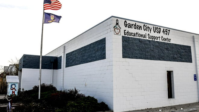 Flags blow in the wind outside the USD 457 Educational Support Center, 1205 N. Fleming St., on Friday  The Garden City school district announced Friday that it would be moving to Level 5 in its COID-19 plan as of Monday.