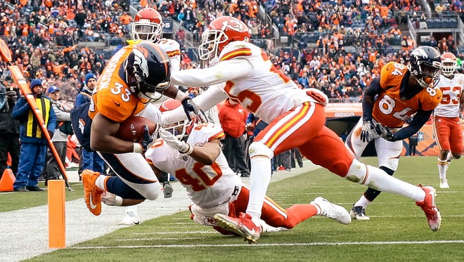 Denver Broncos running back De'Angelo Henderson (33) dives for a touchdown against Kansas City Chiefs cornerback Kenneth Acker (25) and cornerback Keith Reaser (40) in the second quarter at Sports Authority Field at Mile High.