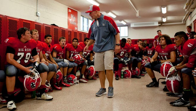 Port Huron coach Ryan Mullins talks to players in the locker room during half time of a football game August 29, 2014 at Port Huron High School.