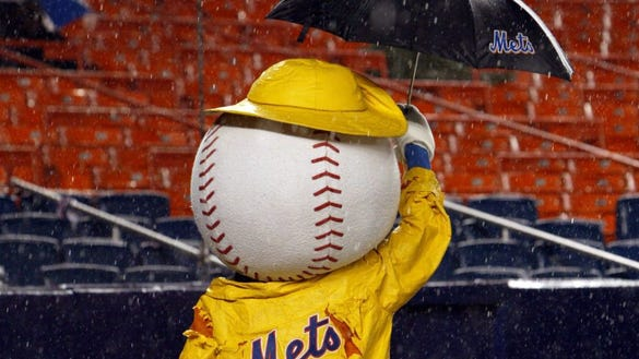 """The New York Mets mascot """"Mr. Met"""" wards off rain with his umbrella during a rain delay of the game between the Philadelphia Phillies and the New York Mets, Monday, May 2, 2005, at Shea Stadium in New York. (AP Photo/Kathy Willens) ORG XMIT: NYKW103"""