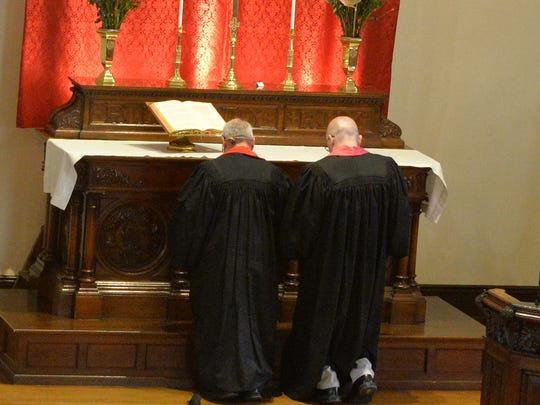 From left, Rev. Bill Long II and Rev. David Jones kneel at the altar of St. John's United Church of Christ, 931 Willow St., Lebanon, during Long's last service as pastor of the church on Sunday, October 30, 2016.