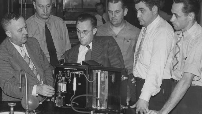 Indiana State Police officers attended a drunkometer operators' school at the Indiana University school of medicine in 1943. Dr. Rolla N. Harger (left) a member of the school's staff nd inventor of the drunkometer shows the officers how the machine works.
