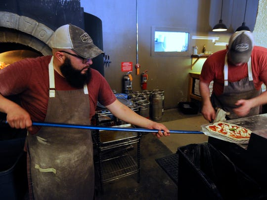 Chef Rob Allen and owner Jason Adams load a fresh pizza onto a peel to go into the oven in June 2017 at Vagabond Pizza.