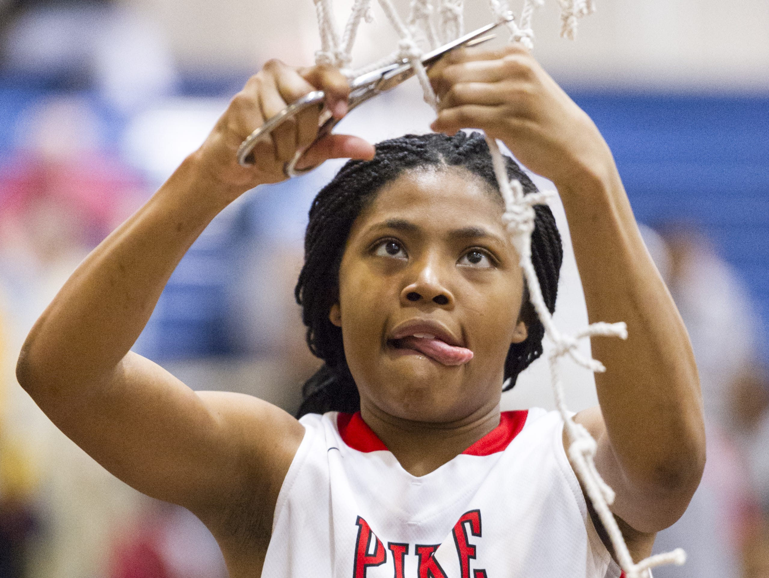 Pike junior Angel Baker (15) cuts down a piece of the net after winning the regional championship against North Central, Feb. 11, 2017. Pike won in overtime, 61-59.