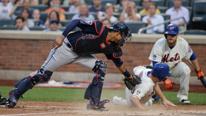 Mets second baseman Daniel Murphy slides safely across home plate for a run ahead of the tag from Braves catcher Christian Bethancourt in the third inning Tuesday.