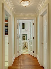 "A hallway was notched out of the large master bedroom suite space, connecting all three rooms in the suite. Since there were no closets in the bedroom, spacious ""his and hers"" closets were added to the hallway."