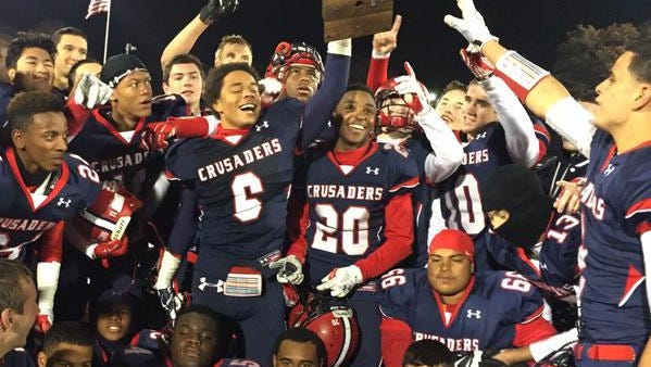 Stepinac's T.J. Morrison (6) hoists the championship plaque after his team won the CHSFL AAA championship over Iona Prep at Fordham University.