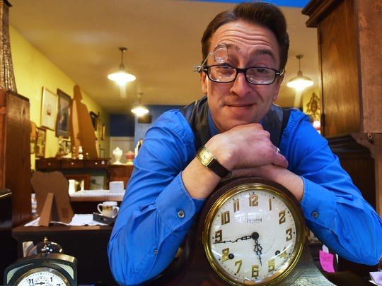 """Tristan Wier of WierClock with one of his pieces of handiwork at Door County Traders Antiques and Consignment Mall  in Sturgeon Bay, where he repairs antique watches and clocks. A clock restored by Wier dating to 1892 is set to appear in the Nov. 30 episoide of the Fox-TV crime drama """"Gotham."""""""