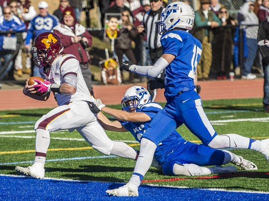 Madison's Ryan Schmitz (4) carries the ball into the end zone with Millburn defender George Hilas (21) at the 85th annual, and final Madison Millburn Thanksgiving Day football game, at Millburn, November 23, 2017.