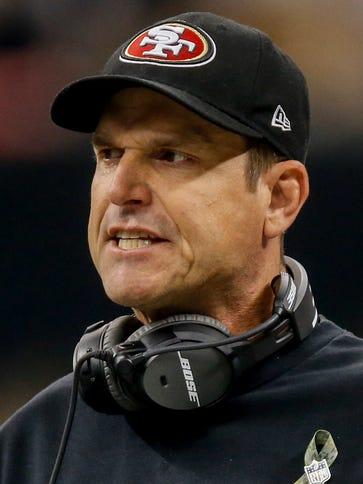 San Francisco 49ers head coach Jim Harbaugh looks on