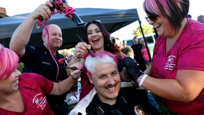 Farmington Police Chief Steve Hebbe has his hair colored pink by Rebecca Ross, left, Farmington Police Department Deputy Chief Keith McPheeters, Hailey Tafoya and Amber Pearson Saturday during National Night Out at Brookside Park in Farmington.