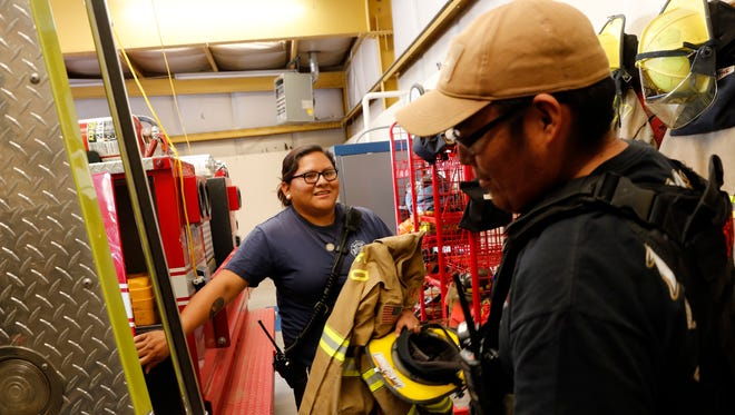 Firefighters Leighann Nez and Derrick Woody collect their gear on Thursday at San Juan County District 12 Fire Department in Shiprock as they prepare to respond to an emergency call.