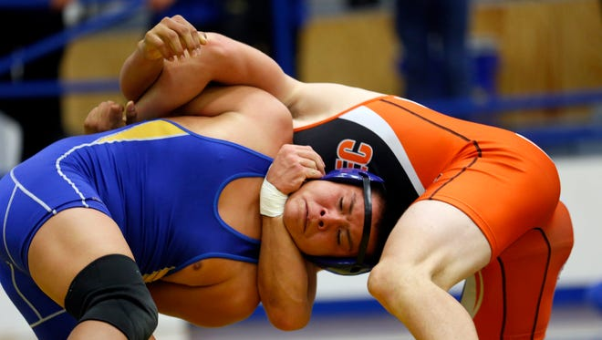 Bloomfield's Jonathan Begaii, left, wrestles Aztec's Josh Snow on Friday during the Bloomfield Invitational at Bobcat Gym in Bloomfield.
