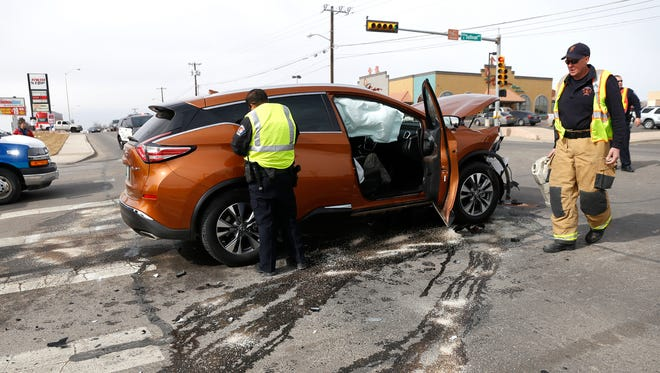 Farmington Police Department and Farmington Fire Department personnel work to clear a two-car injury crash Thursday at the intersection of the East 20th Street and Sullivan Avenue in Farmington.