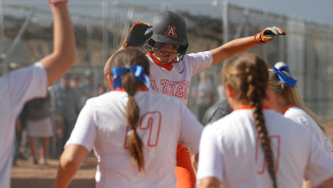 Aztec's Jocelyn Ulrich is greeted by teammates after hitting a home run against Del Norte on Friday at the Aztec Tiger Sports Complex.