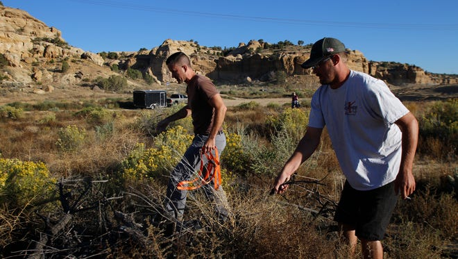 From left, Allen Elmore and Cody DeClusin clean up trash on Sept. 26, 2015, in the Glade Run Recreation Area in Farmington. Elmore has organized a Labor Day weekend cleanup of the area.