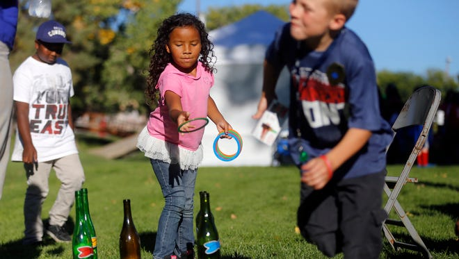 Tee Williams, center, plays a game at the Farmington Police Department's National Night Out last year on Oct. 10 at Brookside Park in Farmington.