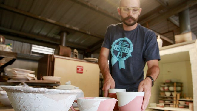 Ceramics instructor Nick Akins loads up a gas kiln with bowls that will be sold at the Hospice Charity Bowl Sale Nov. 4 at San Juan College.