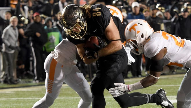Vanderbilt tight end Sam Dobbs (84) crosses the goal line defended by Tennessee defensive back Emmanuel Moseley (12) and defensive back Stephen Griffin (26) in the first half of the game between Vanderbilt and Tennessee at Vanderbilt Stadium Saturday, Nov. 26, 2016, in Nashville, Tenn.
