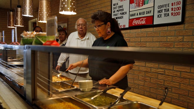 Bernie Sandoval, owner and manager of Chef Bernie's Restaurant, and Drusilla Begay prepare food in the buffet line at Chef Bernie's Restaurant.