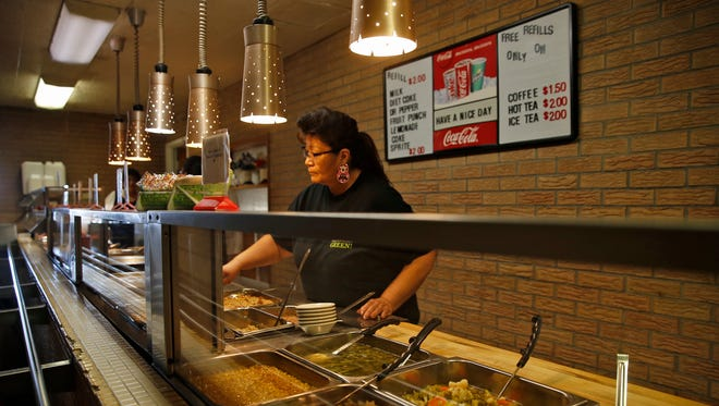 Drusilla Begay prepares food on Monday in the buffet line at Chef Bernie's Restaurant in Farmington.