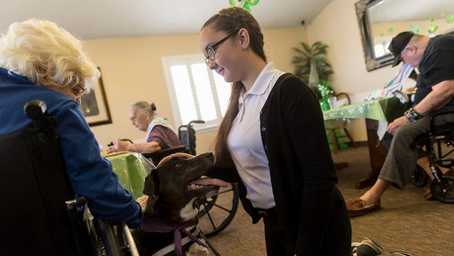 In this Tuesday, March 7, 2017 photo, resident Irma Porter pets Lucy as she and her owner Alexandra Burnham visit residents at the Beehive Homes in Farmington, N.M.