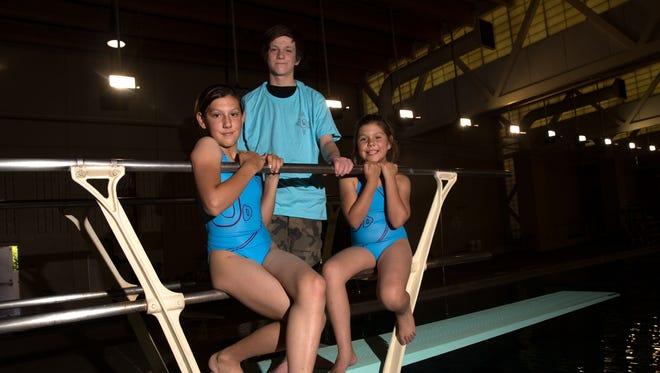 Fuel Diving Club team members, from left, Genevieve Paul, Joe Paul and Juliette Paul pose for a portrait on Wednesday at the Farmington Aquatic Center.