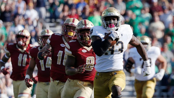 Notre Dame's Josh Adams (33) breaks away from Boston College's Will Harris (8)during the first half in Boston, Saturday.