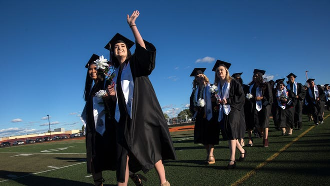 Aztec graduates wave to friends and family as they march, Friday,  in to Fred Cook Memorial Stadium for their commencement cerermony in Aztec.
