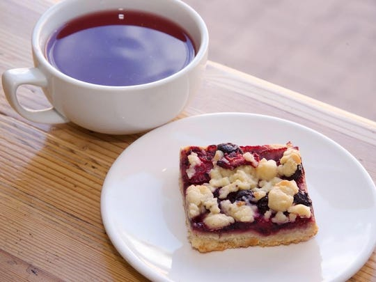 A cup of spicy plum herbal tea with an in-house baked triple berry bar at Songbird Coffee & Tea House.