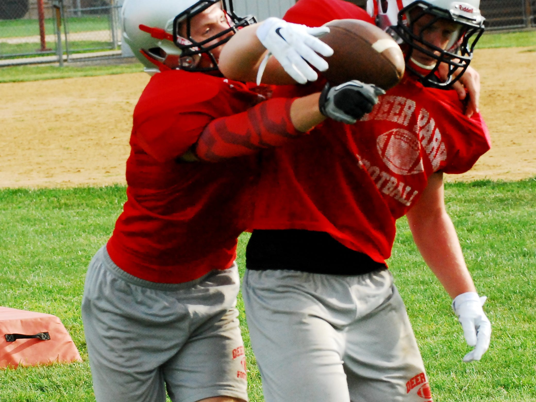 Deer Park senior Austin Siemon, back, works to strip his teammate Tanner Hicks, front, of the ball during Wildcat practice.