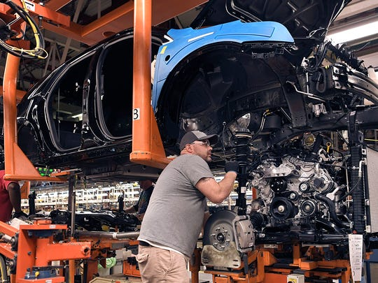 A worker places engines into Cadillac XT5 and GMC Acadia