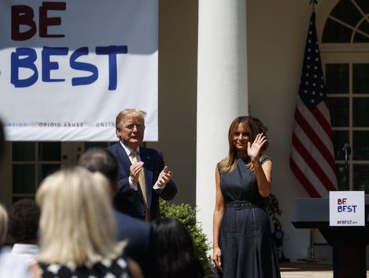 President Donald Trump applauds first lady Melania