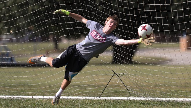 Carter Alvey, 17, a soccer goalkeeper at Bethlehem High School in Bardstown, bats down an attempt during practice.  He has cerebral palsy and has tried out for the U.S. Paralympic team.