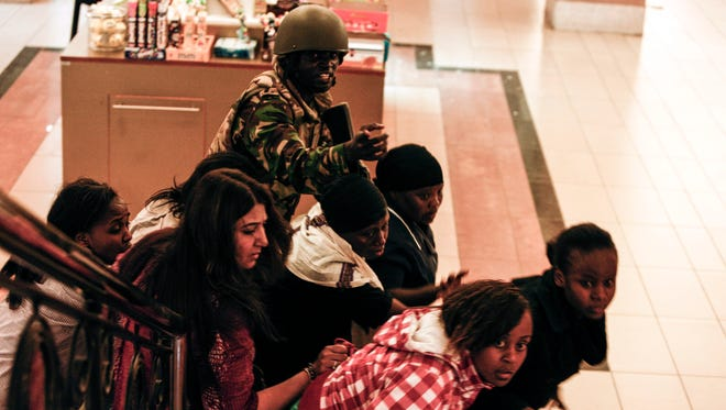 A soldier directs people up stairs inside the Westgate mall after a shootout in Nairobi.