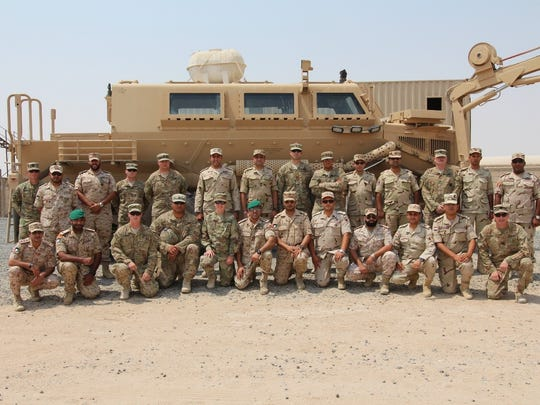 Egyptian and Kuwaiti officers pose with soldiers from Bravo Company, 2nd Engineer Battalion behind a Buffalo vehicle.