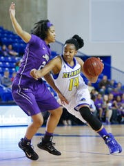 James Madison's Aneah Young (left) defends as Delaware's Alecia Bell in the fourth quarter of the Blue Hens' 65-43 loss at the Bob Carpenter Center Wednesday.
