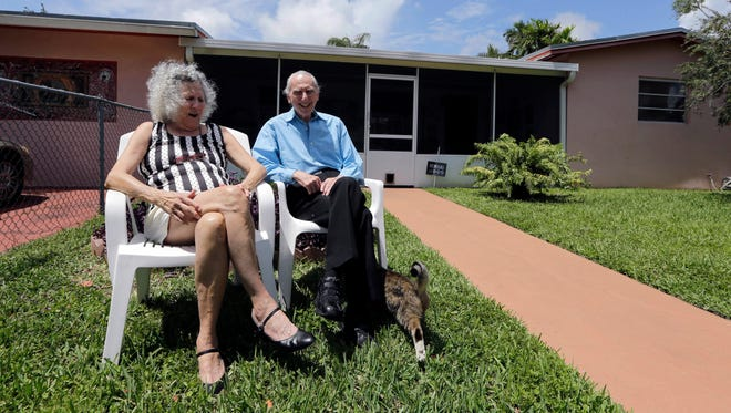 Al Karp, right, and wife Saundra, pose in front of their home in North Miami Beach, Fla.